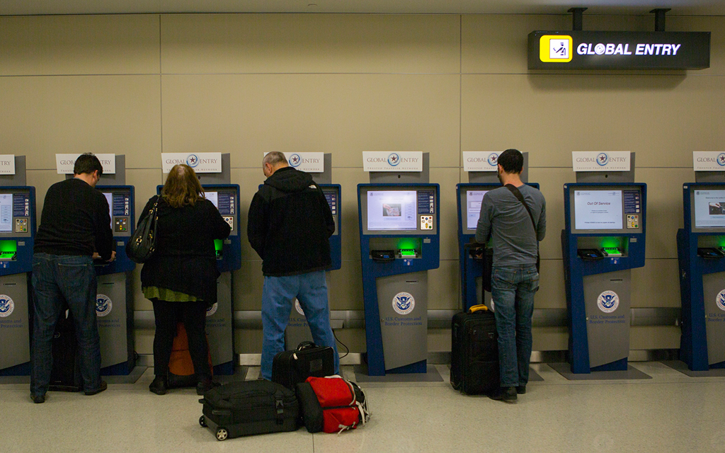 Travelers standing at Global Entry Kiosks at an international airport